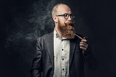 istock A man smoking pipe over grey background. 1074591812