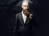 istock A man smoking pipe over grey background. 1074591852