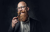 istock A man smoking pipe over grey background. 1074593982