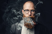 istock A man smoking pipe over grey background. 1074594032