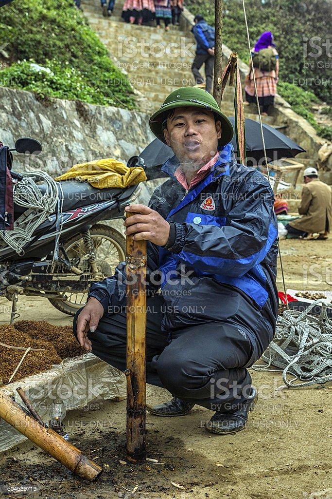 Man smoking tobacco in large pipe. stock photo