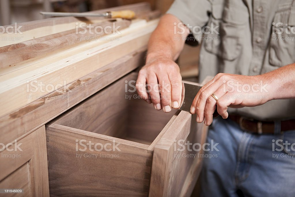 Man smoothing wood cabinet with scraper stock photo