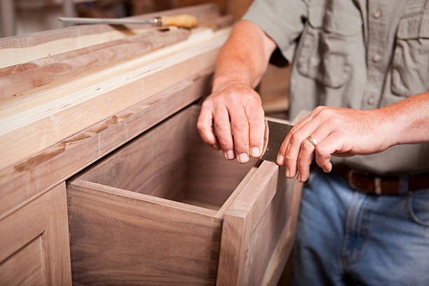 man smoothing wood cabinet with scraper - customize stock pictures, royalty-free photos & images