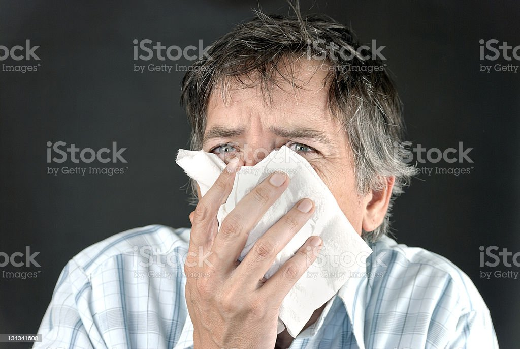 Man Sneezes Into Tissue Front royalty-free stock photo