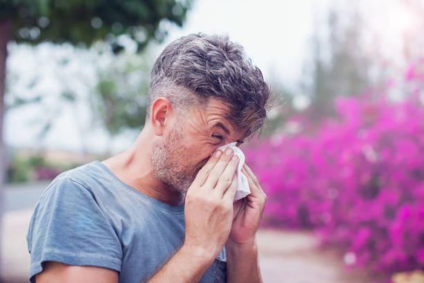 mann in einem gewebe im freien niesen. pollenallergie, frühling. - heuschnupfen stock-fotos und bilder