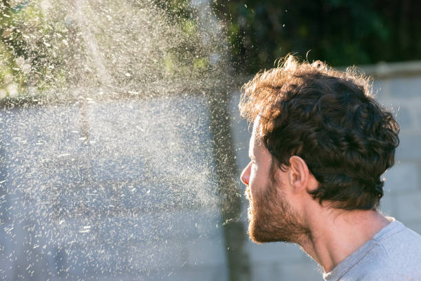 Man sneezing spray cloud Coronavirus transmission germs Man sneezing without a mask, sneeze spray cloud  backlight. Airborne germs mucus stock pictures, royalty-free photos & images