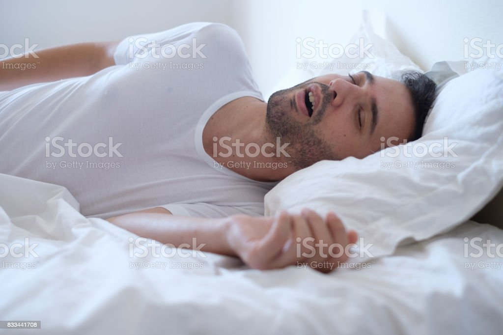 Mann wegen Apnoe im Bett liegend Schnarchen – Foto