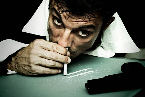 Man Snorting Cocaine Off Table stock photo