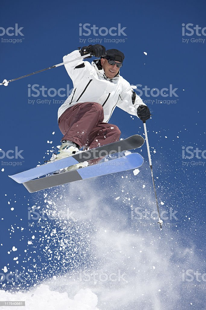 Man Snow Skiing Against A Blue Sky royalty-free stock photo