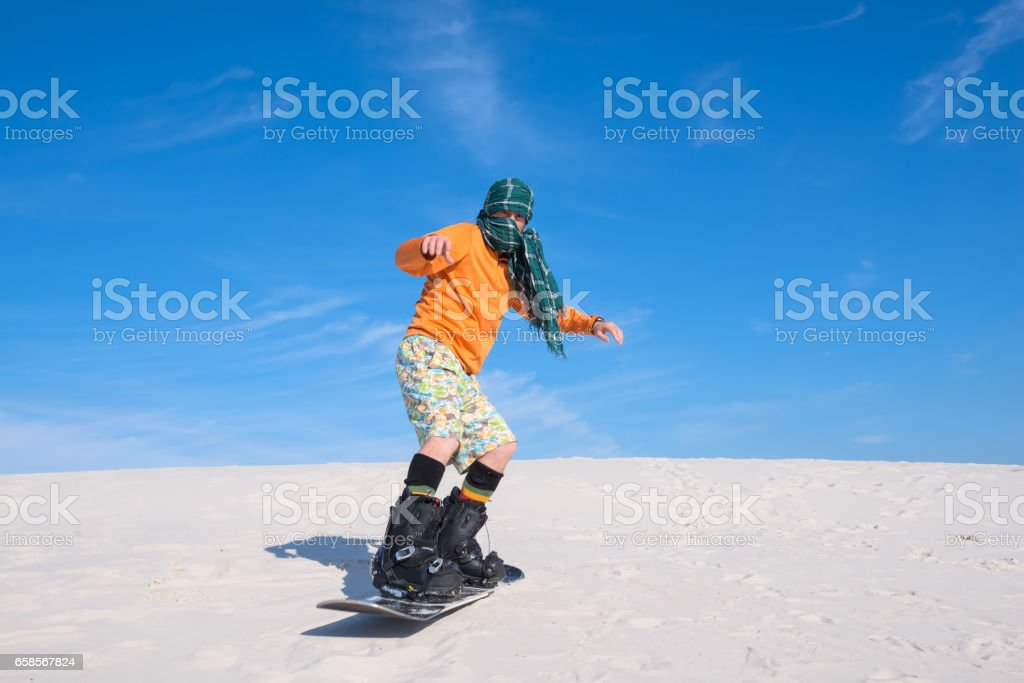 Man wearing a scarf engaged in snowboarding amongst the sand dunes...