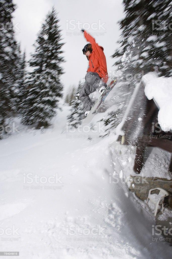 Man snowboarding off roof foto de stock royalty-free