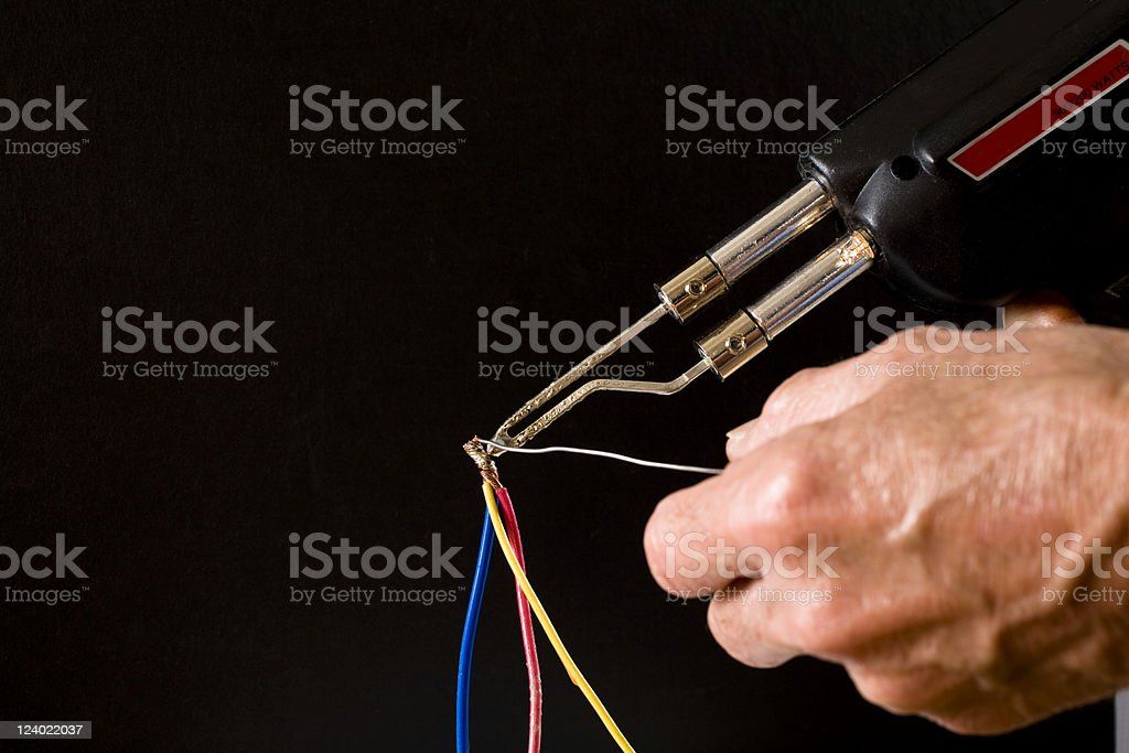 Man soldering copper wires together stock photo