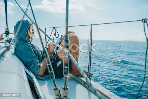 Man solving crossword puzzle on boat