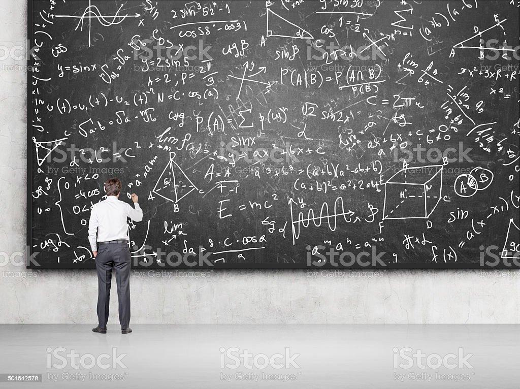 Man solving problems on blackboard stock photo