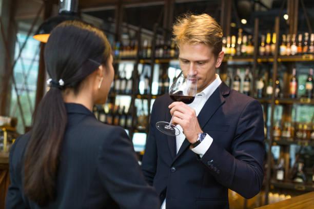 Mann-Sommelier Verkostung Rotwein mit Emotion zu entspannen. Der Mann hält Weinglas und Geruch. Mann mit Sommelier und Weinkonzept. – Foto