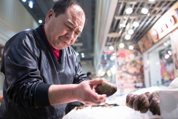 hombre tipo productos frescos para la venta en el mercado de pescado de tsukiji, tokio, japón - pez sierra fotografías e imágenes de stock