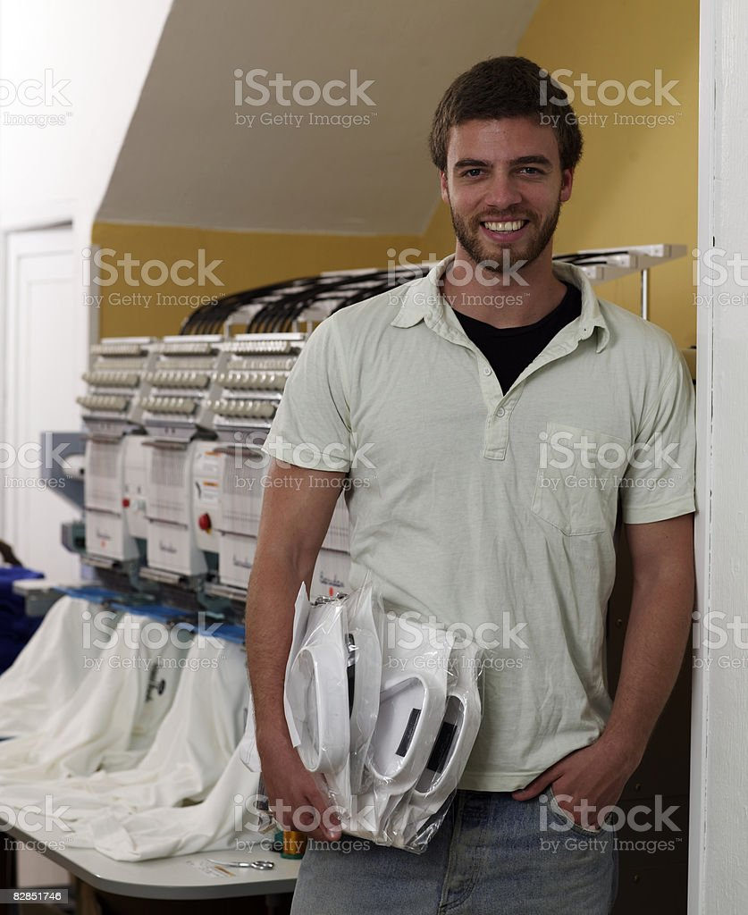 Uomo mette le camicie a un servizio di sartoria su misura foto stock royalty-free