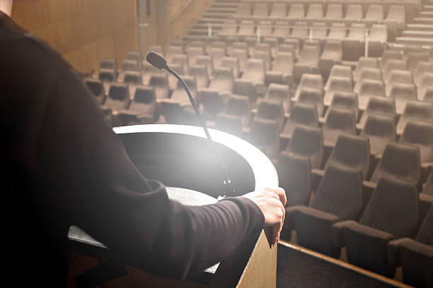 Man speaker testing its speech Close-up of unrecognizable man speaker on pupitre, testing its speech before conference, with microphone front empty seating of a common amphitheater. pulpit stock pictures, royalty-free photos & images