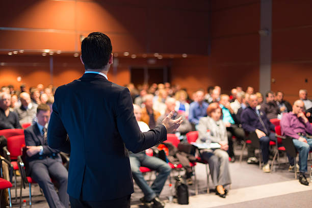 A man speaking at a business conference stock photo