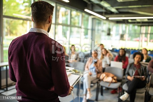 istock Man Speaking in front of Audience 1147294133