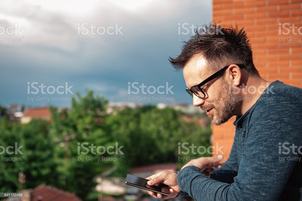 Man speaking into smart phone stock photo