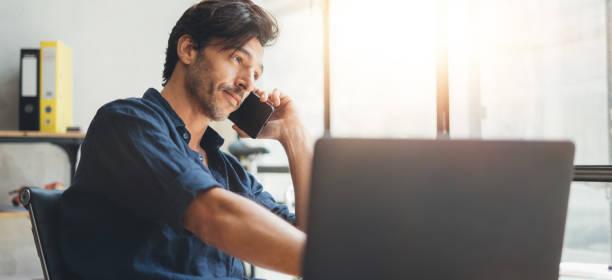 Mann spricht am Telefon im hellen Büro – Foto