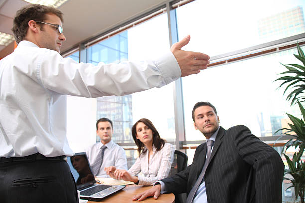 Man speaks in front of colleagues stock photo