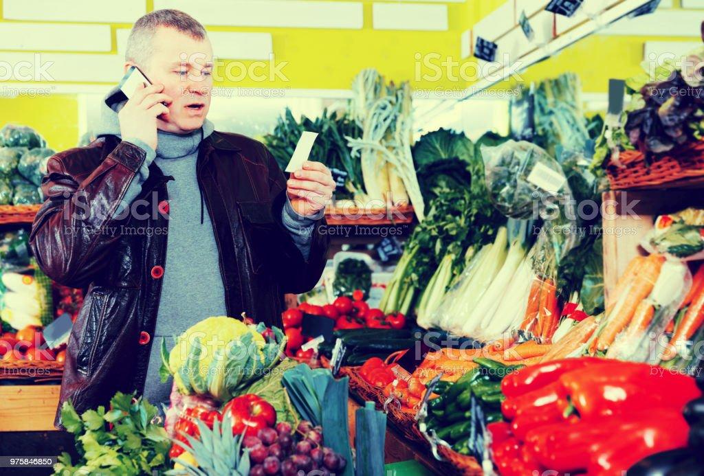 Mann, die Einkaufsliste im Shop angeben - Lizenzfrei Aussuchen Stock-Foto