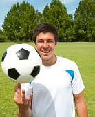 Man spinning a soccer ball on his finger on soccer field