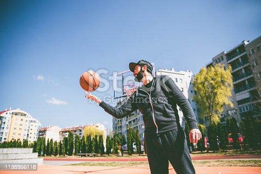 Man spinning  basketball on finger.