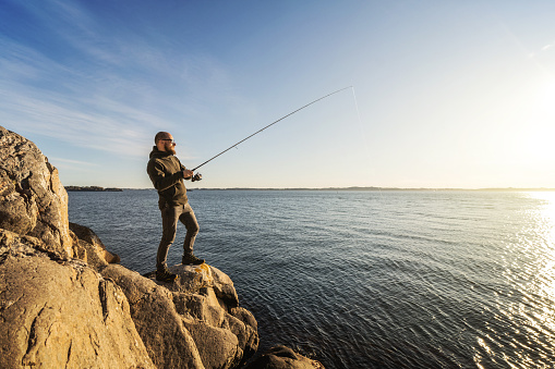 Man spinning fishing in the sea with a rod, from the rocks