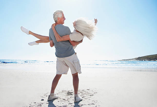 Man spinning woman on beach stock photo