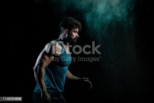 618209684 istock photo Man splashing colorful powder 1145254958