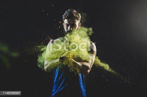 618209684 istock photo Man splashing colorful powder 1145255337