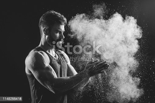Handsome strong man splashing color dust