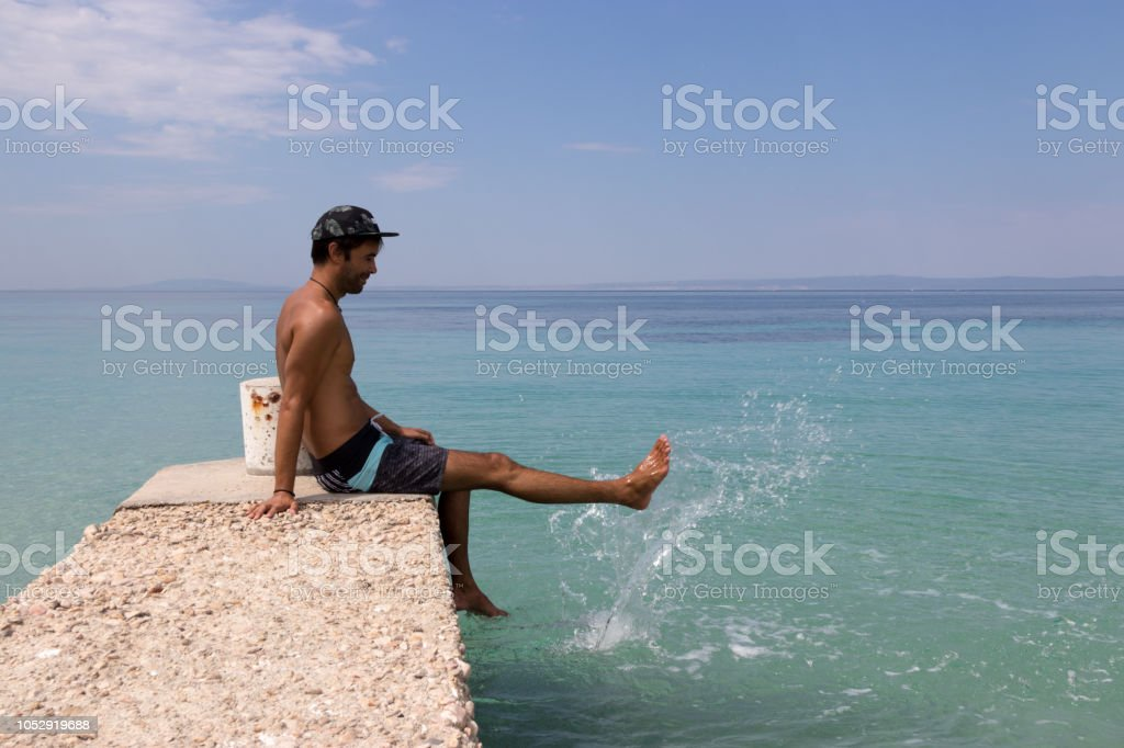 Man splashing sea water with his leg stock photo