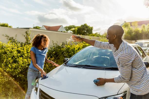 Mann spritzt Wasser auf Frau beim Putzen Auto – Foto