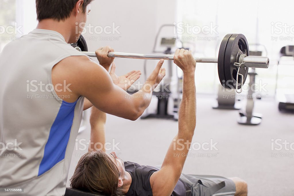 Man spotting friend lifting barbell in gymnasium stock photo