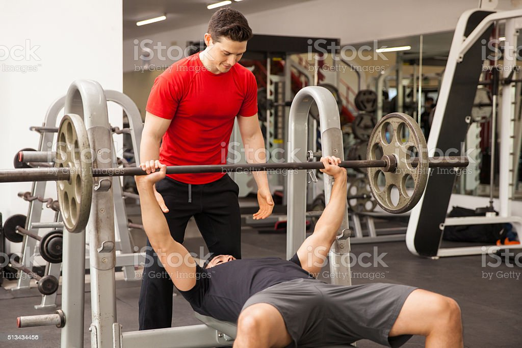 Attractive Man Spotting His Friend On A Bench Press Royalty Free Stock Photo