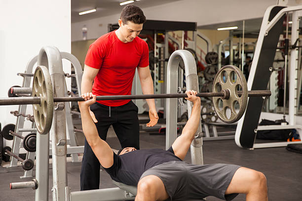 Man spotting his friend on a bench press stock photo