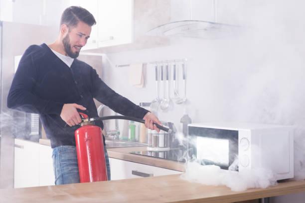 man spraying fire extinguisher on microwave oven - burned oven imagens e fotografias de stock