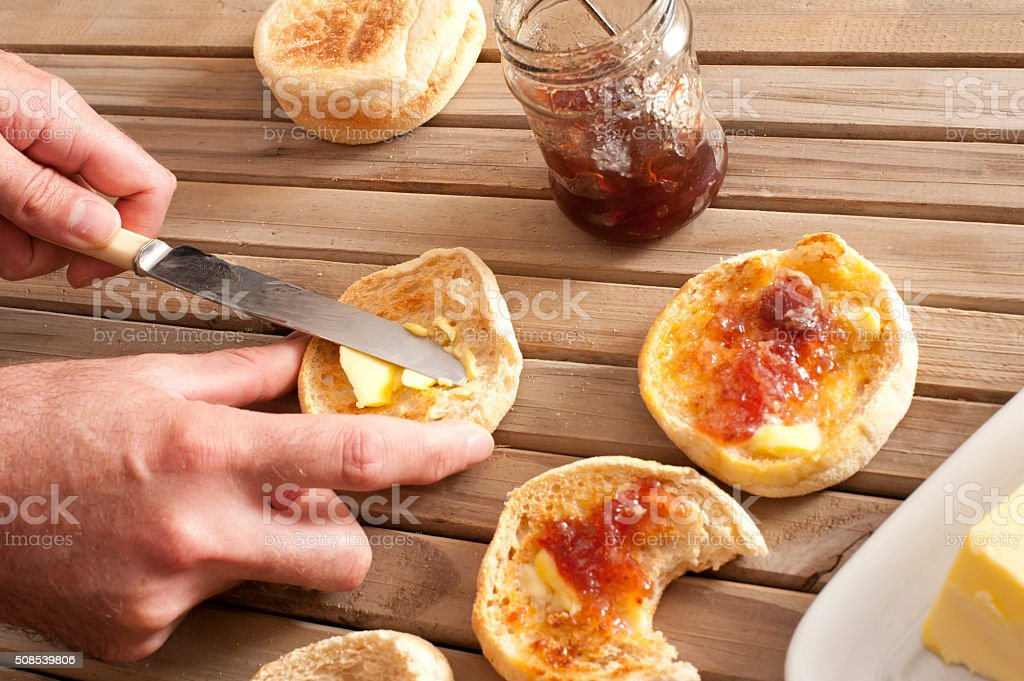 Man spreading crumpets with jam and butter stock photo