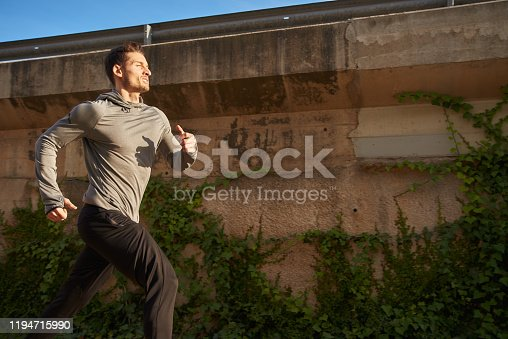 Man in athletic gear sprinting passed a brown city wall covered in green shrubbery