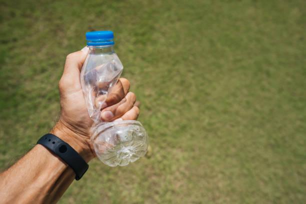 homem aperta em sua mão uma garrafa de plástico vazia em um fundo de grama verde. - squeeze bottle - fotografias e filmes do acervo