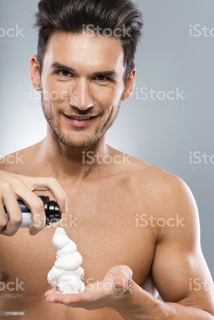Man squeezes shaving cream in hand royalty-free stock photo