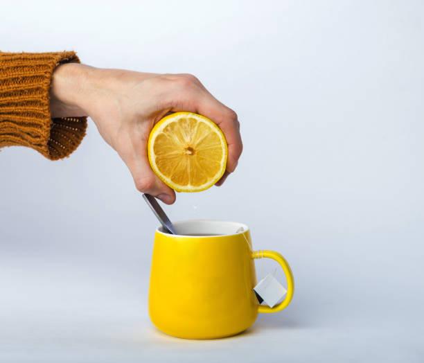 man quetschen zitrone in tee in gelber teetasse. die hand des mannes in eine warme strickpullover isoliert auf grau. konzept zur vorbeugung von grippe und erkältung - heiße zitrone stock-fotos und bilder