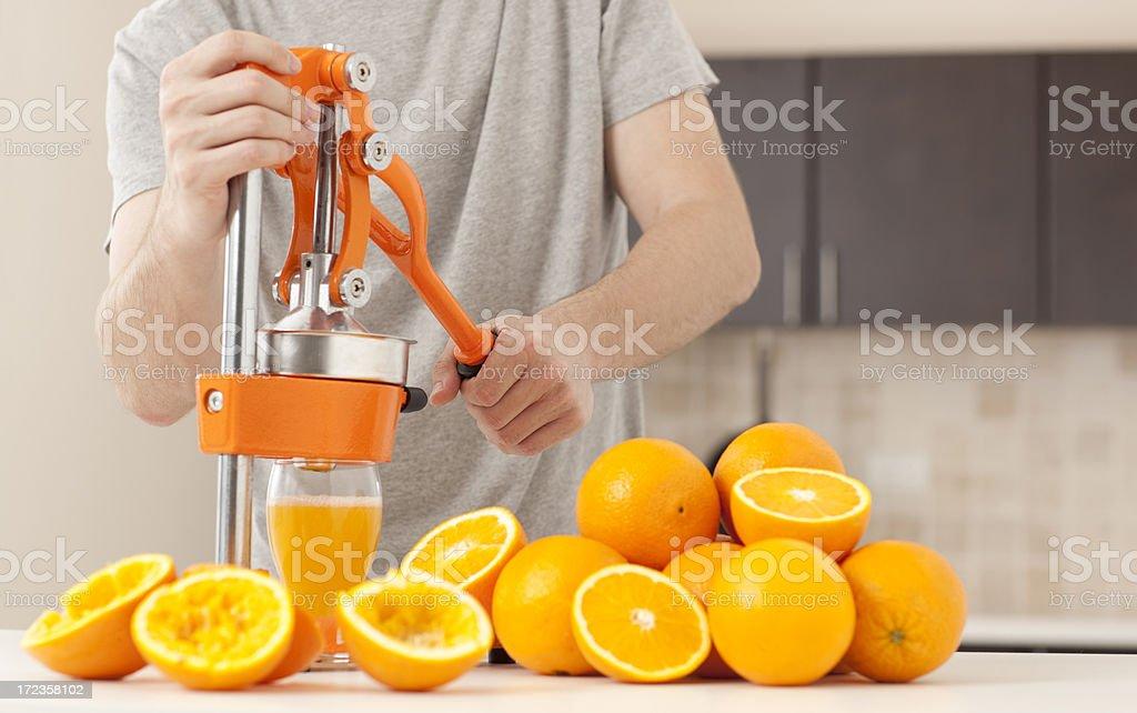 Man squeezing orange slices to make juice. stock photo