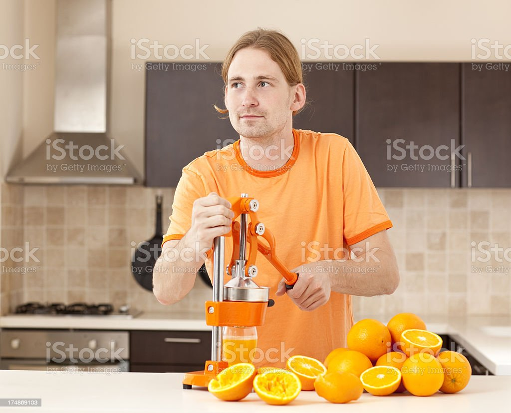 Man squeezing orange slices to make juice stock photo