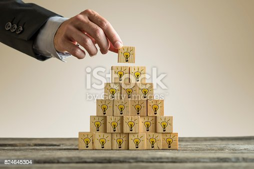 istock Man stacking a tower with yellow light bulbs in a form of a pyramid 824645304