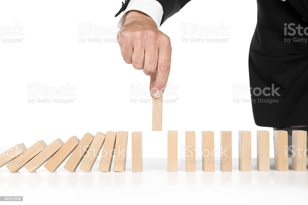 Man stacking wooden domino tiles preventing a fall stock photo